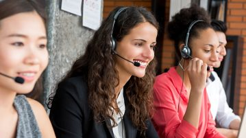 Multi-ethnic agents speaking with clients on the phone in call center.